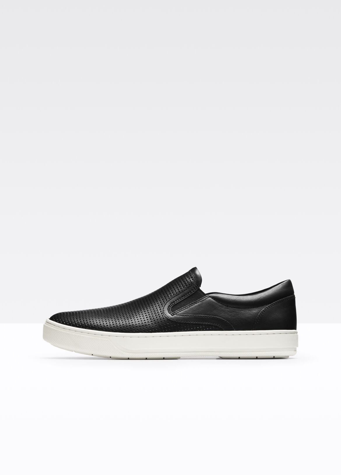 Blocked with contrasting perforated and smooth Italian leather; signature slip-on sneaker set on a thick rubber sole.